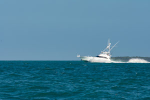 Fishing boat with a high fishing tower going over the water